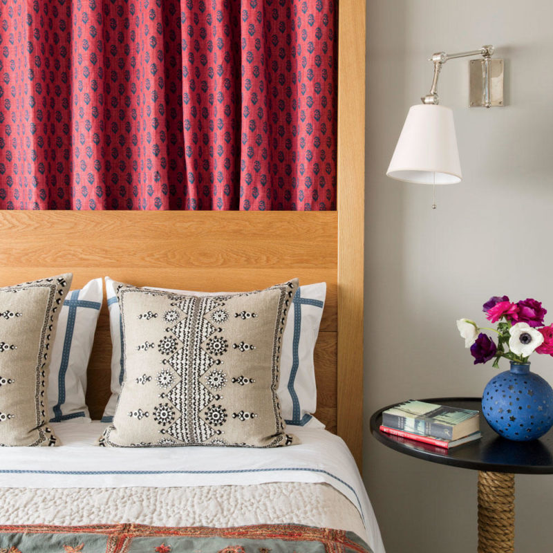tight view of bed with hardwood corner post and headboard, patterned red curtains behind bed, night table with blue vase of flowers, patterned duvet cover and throw pillows.