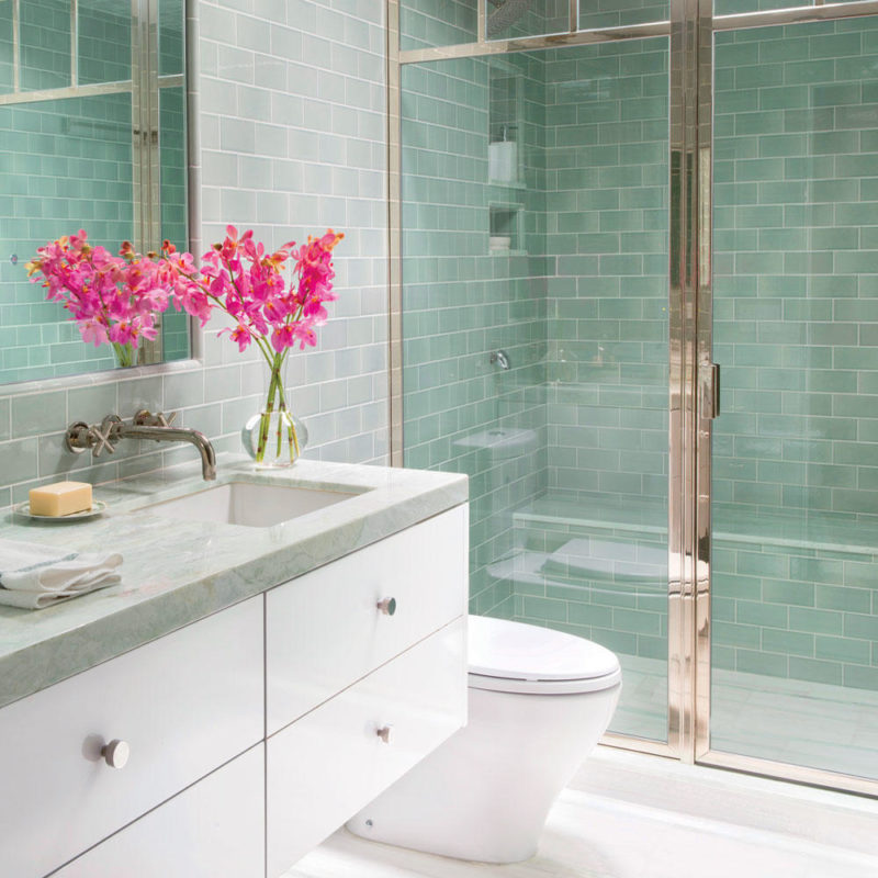 Light green tile walled bathroom with chromed frame glass shower, stone countertops and floor tiles, ceiling window light, white drawers and toilet.
